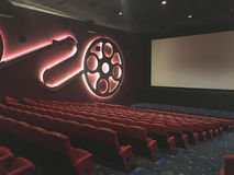 Entertaiment. View of interior cinema hall with rows of red seat in low light condition before the movie starts Stock Image