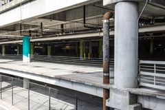 View into interior of an empty parking garage with pipes and chain link fencing Stock Photos