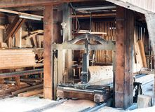 View of an traditional old saw mill with old machines and tools. A view of the interior of an old traditional saw mill with old machines and tools royalty free stock images