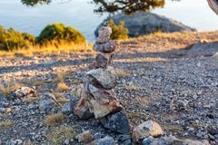 View on inuksuk pyramid of rocks in balance and bushes lit wit. H setting sun light on stony path above Black sea in Crimea at sunset Royalty Free Stock Photos