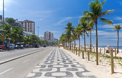 Ipanema beach with palms and mosaic of sidewalk in Rio de Janeiro Stock Images