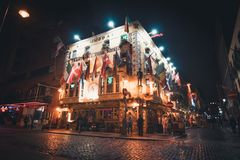 View of an Irish pub with flags and lights in Dublin. Dublin, Ireland - September 2018. View of an Irish pub with flags and lights at night, located on the stock photography