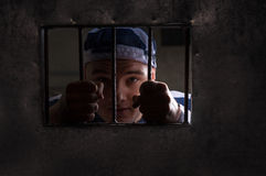 View through iron door with prison bars on male prisoner holding. Bars wearing prison uniform in a jail cell Royalty Free Stock Photography