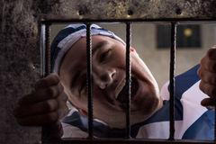 View through iron door with prison bars on male prisoner holding. View through iron door with prison bars on male prisoner wearing prison uniform holding bars Stock Photography