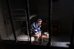 View through iron door with prison bars on male wearing prison u. Niform sitting on a bed near bedside table with aluminum dishes in a small jail cell stock photo