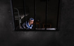 View through iron door with prison bars on man wearing prison un. Iform sitting on a bed near bedside table with aluminum dishes in a small jail cell Royalty Free Stock Photos