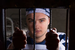 View through iron door with prison bars on young male prisoner h. Olding bars wearing prison uniform in a jail cell royalty free stock image