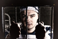 View through iron door with prison bars on young prisoner holdin. G bars wearing prison uniform in a jail cell royalty free stock photos