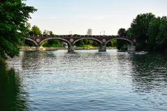 View of the Isabella Bridge that crosses the Po river at dusk with a few canoeists paddling and doing sports. stock photos