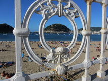 View of Isla de Santa Clara through the railing on Playa de la Concha, San Sebastian Stock Photos