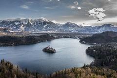 View on island with church in the middle of Lake Bled among the mountains in snow. Stock Image