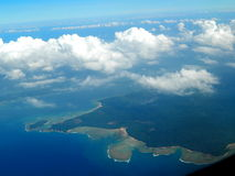 View of island and clouds together from airplane Royalty Free Stock Photo