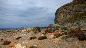 View of the island of Gramvousa, Crete - boulders, stones, bushes of bright red color and the sea in the background Royalty Free Stock Photo