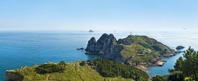 View of  island lighthouse from mountain top on sunny day Stock Images