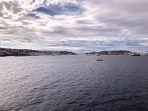 View of the island of Mykonos Greece from the sea. Cloudy clouds in the sky over the island. royalty free stock photos