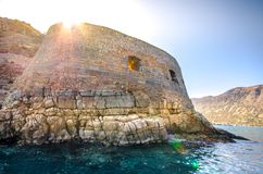 View of the island of Spinalonga with calm sea. Here were isolated lepers, humans with the Hansen`s desease, gulf of Elounda. View of the island of Spinalonga Stock Photos