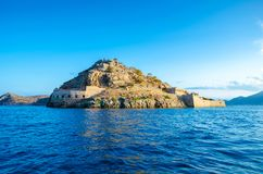 View of the island of Spinalonga with calm sea. Here were isolated lepers, humans with the Hansen`s desease, gulf of Elounda. View of the island of Spinalonga Stock Photography