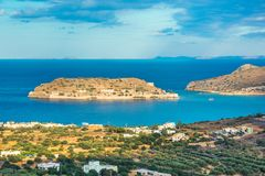 View of the island of Spinalonga with calm sea. Here were isolated lepers, humans with the Hansen`s desease, gulf of Elounda. Panoramic view of the gulf of Stock Images