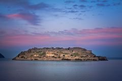 View of the island of Spinalonga at night with nice clouds and calm sea. Here were  lepers. View of the island of Spinalonga at night with nice clouds and calm Royalty Free Stock Photo