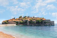 View of the island of Sveti Stefan from the opposite shore and parked boats near it.  royalty free stock image