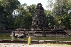 View of the island temple Preah Neak Poan with jungle in background. Scene around the Angkor Archaeological Park. The site contains the remains of the different Royalty Free Stock Image