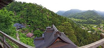 View of japanese buddhist temple in Yamadera with beautiful land. Yamadera, Japan - June 28, 2010: Panoramic photo of the roofs of the famous Yamadera buddhist Stock Image