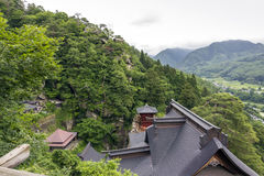 View of japanese buddhist temple in Yamadera with beautiful land. Yamadera, Japan - June 28, 2010: Roofs of the famous Yamadera buddhist temple complex in Tohoku Stock Images