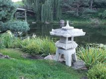 Stone lantern in Japanese garden. View of Japanese garden with water pond a bridge and a stone lantern in a foreground Royalty Free Stock Images
