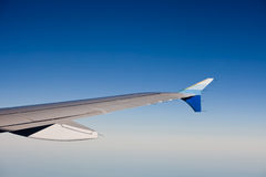 View of jet airliner wing in flight. View of a wing of commercial jet airliner in flight on a blue sky background Royalty Free Stock Photos
