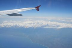 View of jet plane wing with land and sea below Stock Image