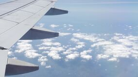 Jet Plane Wing and White Clouds