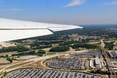 View from jet window flying over land and water Royalty Free Stock Photos