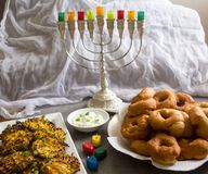 Jewish holiday Hanukkah symbols against white background; traditional spinning top, menorah traditional candelabra, `Sfinj `Donu royalty free stock image
