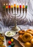 Jewish holiday Hanukkah symbols against white background; traditional spinning top, menorah traditional candelabra, `Sfinj `Donu stock photography