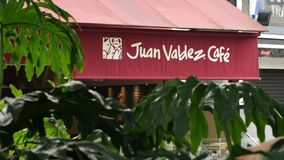 View of `Juan Valdez` coffee shop in tropical setting stock footage