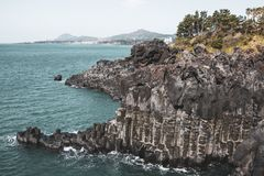 View of the Jusangjeollidae. Jusangjeolli are stone pillars piled up along the coast and is a designated cultural monument of Jeju. Island. Jusangjeolli Cliff stock images