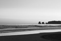 View just before sunrise of silhouette deux jumeaux in summer sky on a sandy beach in black and white Stock Photography