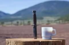 A k bar knife and the morning coffee. A view of the k bar knife and morning coffee sitting and waiting on the desert wooden log royalty free stock photography