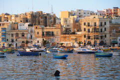 The view of Kalkara city over the Kalkara bay in the sunset ligh. KALKARA, MALTA - JULY 23, 2015: The view of Kalkara city over the Kalkara bay with moored ships Stock Image
