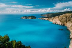 View of Kefalonia west coastline. Assos village town and Frourio peninsular. Beautiful milky blue bay with brown rocky. Limestone costline and moving white royalty free stock image