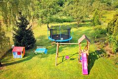 View of kids playground in green backyard garden with birch trees and flower bed. Stock Images