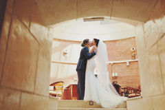 A view on the kissing couple standing in the corridor's tunnel Royalty Free Stock Images