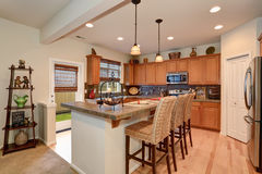 View of kitchen with hardwood storage combination, bar and pendant lights. View of kitchen with hardwood storage combination, brown shelf with decor, bar and stock photo