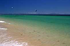 View of kite surfers from a white sandy beach in Spain, Europe, on a hot sunny day on vacation. Stock Photos