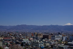 View of Kofu Japan. View of smal Japanese city, Kofu, with mount Fuji in distance, blue sky stock photo