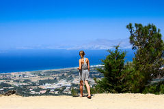View from Kos. Teenage girl standing on a Kos hilltop looking across the Aegean sea towards the island of Kalymnos Stock Images