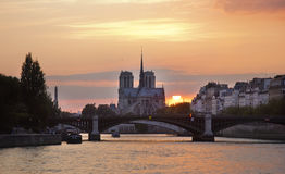 View of the cathedral Notre-Dame de Paris. Sunset on the Seine. Stock Photos