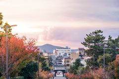 View of Kyoto City at sunset in Japan. View of Kyoto City, Japan at sunset from Kacho-michi street in Gion in autumn, with a mountain and clouds in the distance stock photos