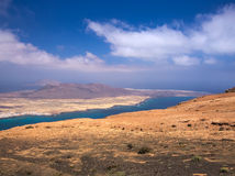 View of the La Graciosa island from a slope of Mount Mirador del Rio on background blue sky and Atlantic Ocean Stock Images