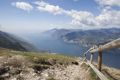 View of Lago di Garda from Monte Baldo with a wooden fence. Blue sky and nicely shaped clouds Royalty Free Stock Image
